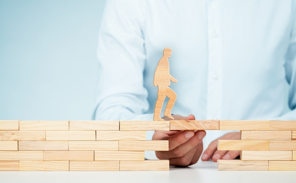 model wooden person walking across blocks held up by doctor